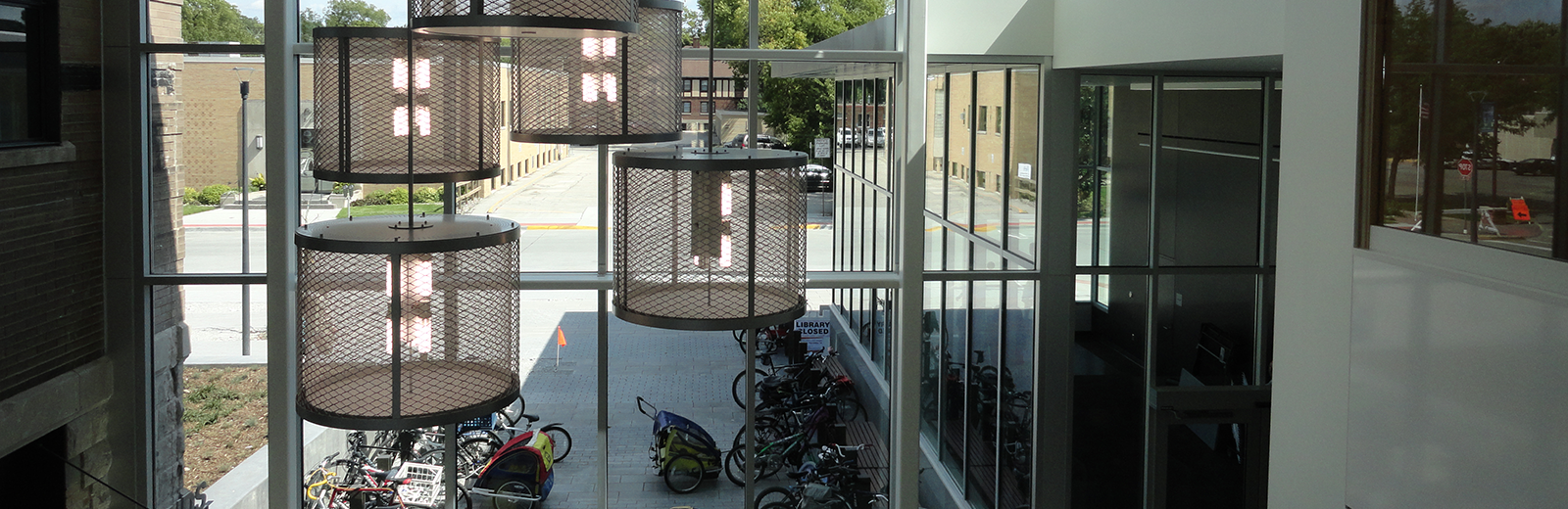Bike racks seen through chandeliers and glass of Ames Pubic Library