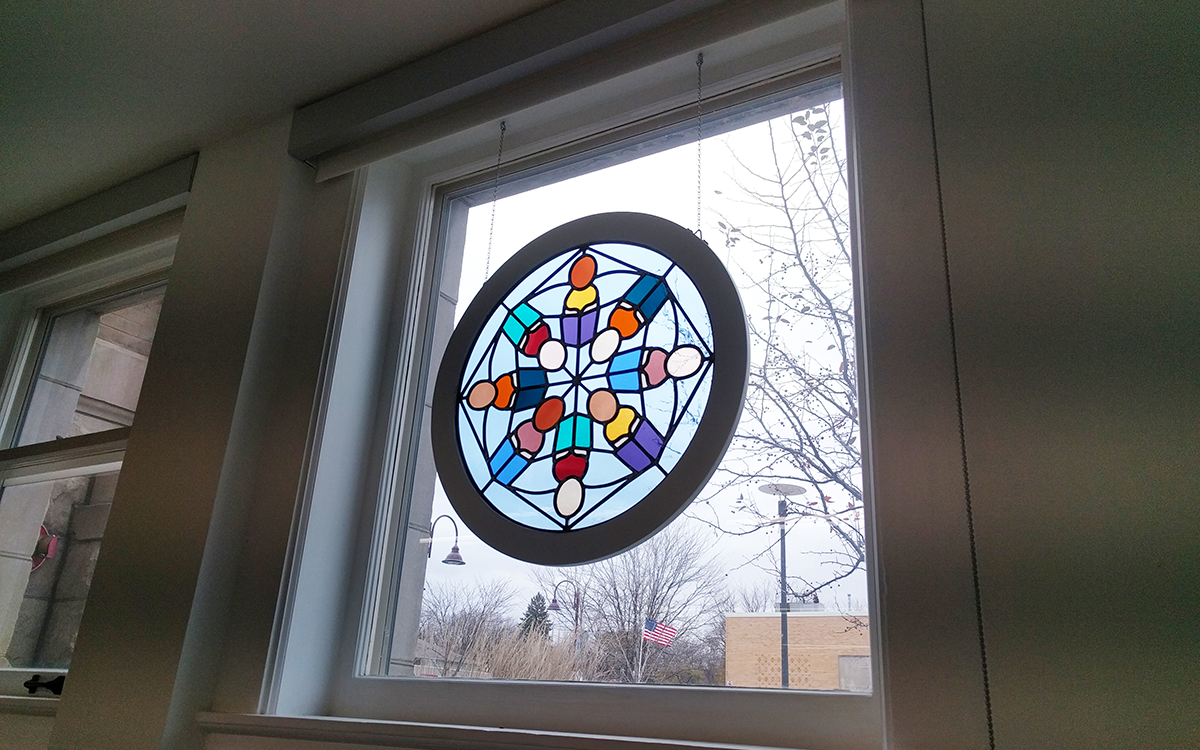 Stained glass kaleidoscope hanging in window