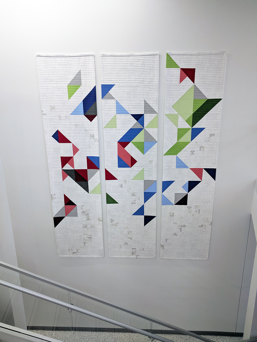 Quilt with geometric design hanging on wall