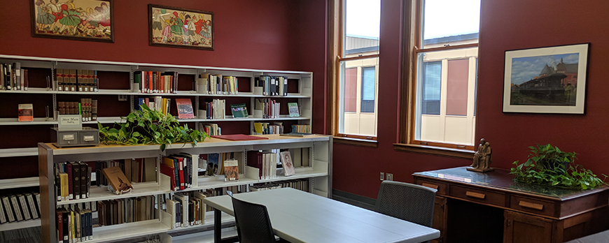Heritage Room filled with books, two desks, and historical artwork