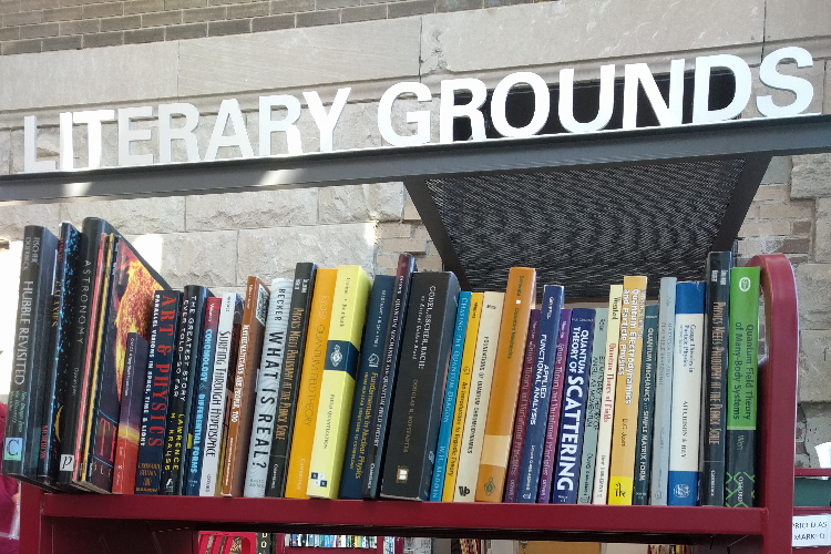 Photo of Literary Grounds metal text sign above cart of books