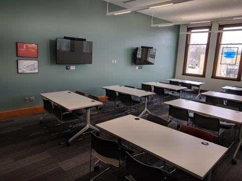 Danfoss Room with classroom style room setup and two mounted screens