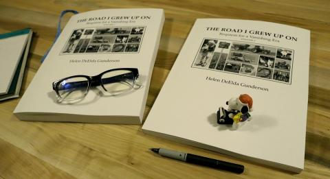 The Road I Grew Up On: Requiem for a Vanishing Era books on table with pen, glasses, and figure of Snoopy with a typewriter